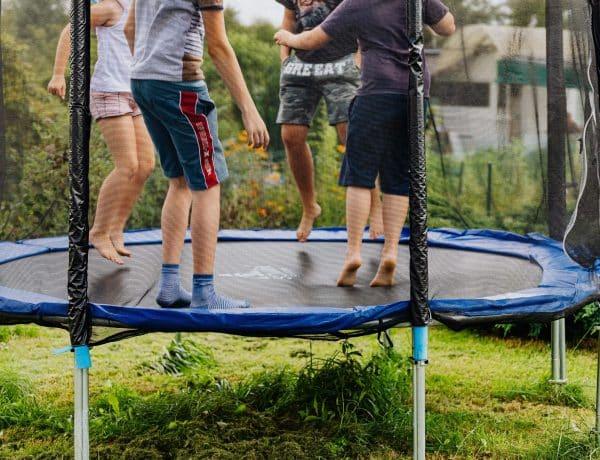 kinds on trampoline in garden